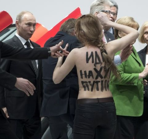 Putin grins at bare-breasted protester